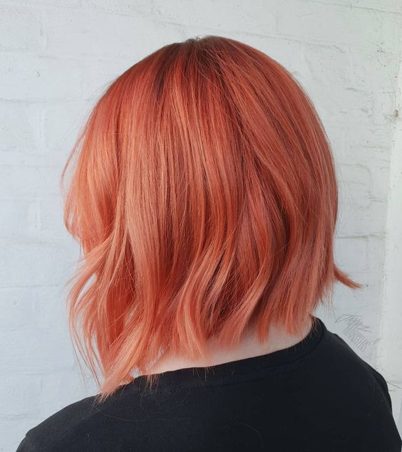 Girl from behind showing her short hair dyed with peachy copper dye