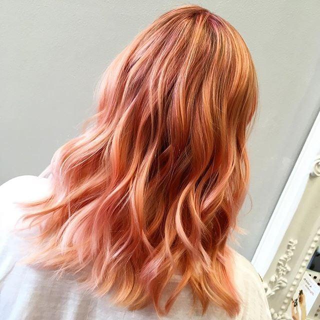 Chica de espaldas mostrando su cabello largo teñido en estilo peachy copper