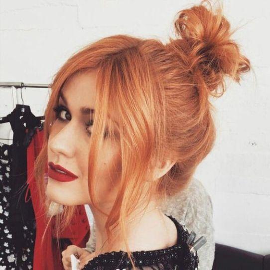 Chica con cabello peinado en bun y teñido en efecto peachy copper