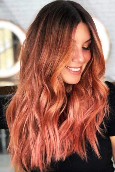 Chica sonriendo mostrando su cabello teñido en peachy copper
