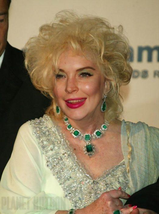 Lindsay Lohan caracterizada como una mujer de edad adulta con canas y un vestido de color verde con joyas