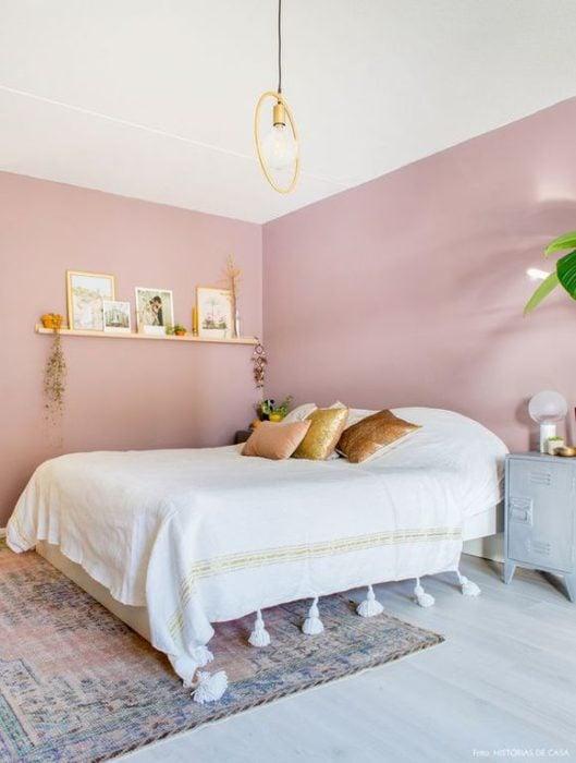 Habitación rosa con una cama de color blanco