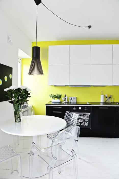 Cocina con colores verde limón en las paredes y muebles de color blanco con negro