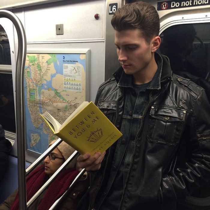 Chico leyendo un libro dentro del metro y llevando chamarra negra
