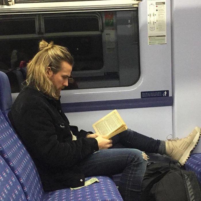 Hombre de cabello largo con peinado estilo bun leyendo dentro del metro