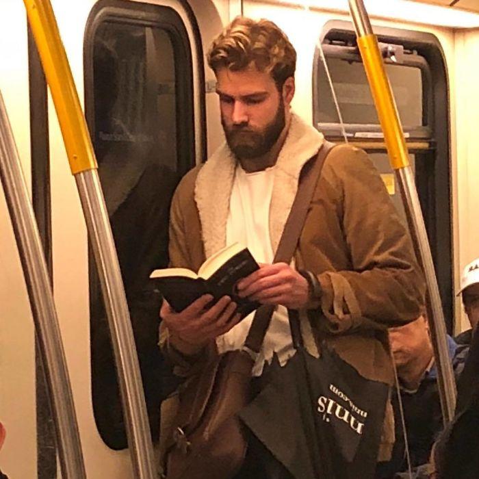 Chico con barba abultada recargado en la puerta del metro leyendo un libro