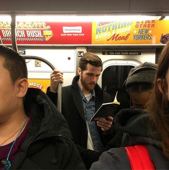 Chico con chamarra negra leyendo en el metro