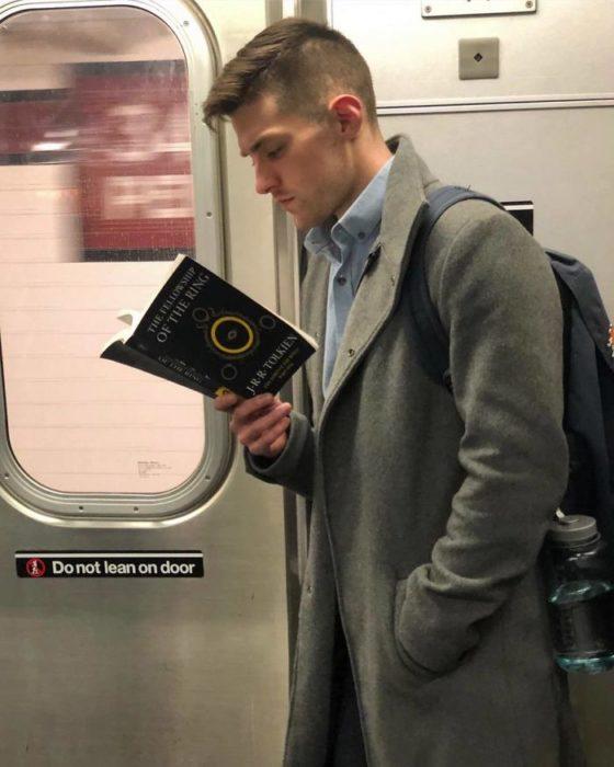 Hombre con gabardina gris y camis a azul leyendo en el metro
