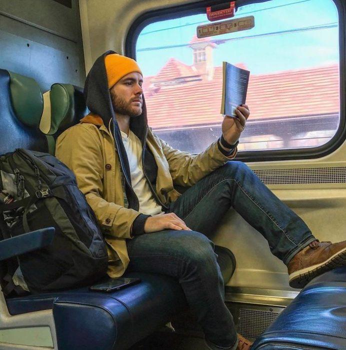 Hombre con chaqueta amarilla mostaza leyendo dentro del metro