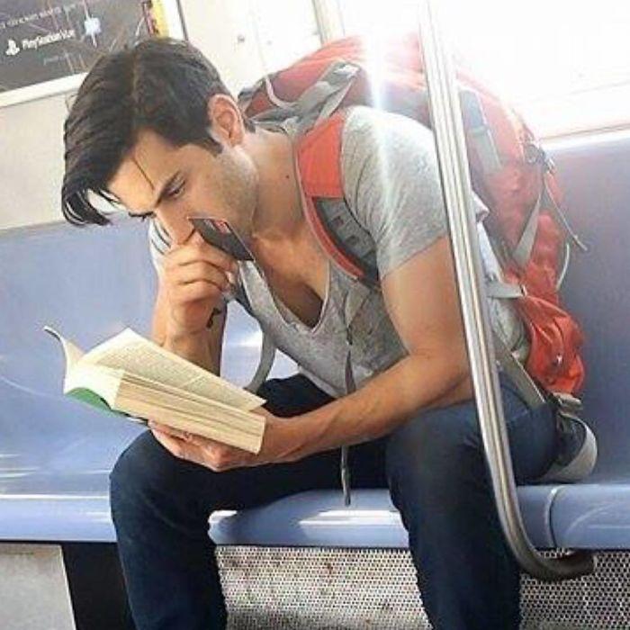 Hombre sentado en el asiento del metro leyendo un libro