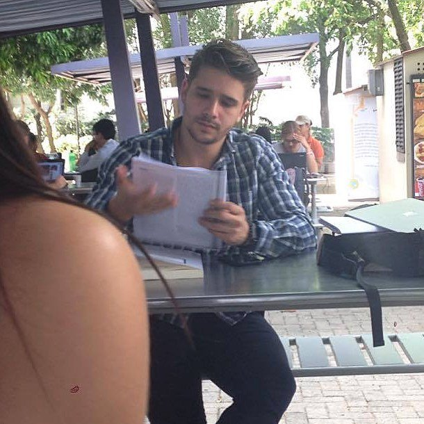 Chico con camisa a cuadros leyendo en el patio de la escuela