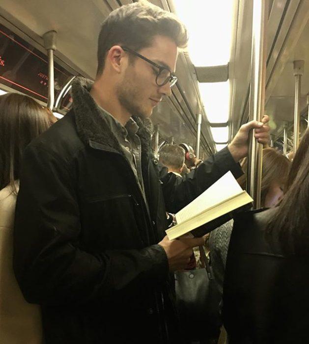 Hombre con gafas sostenido de una barra de metal y leyendo un libro