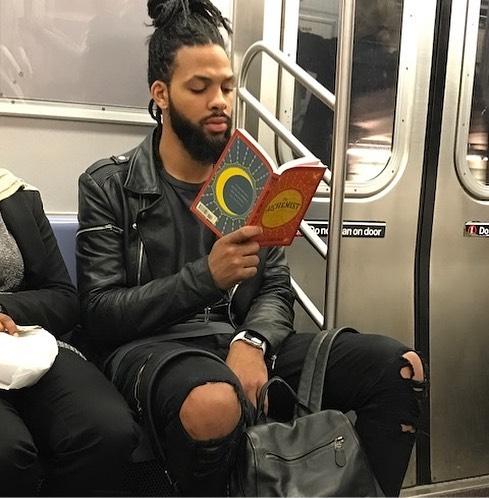 Hombre con jeans rotos leyendo dentro del metro