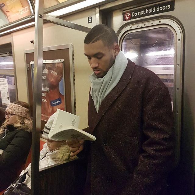 Hombre llevando bufanda azul cielo y abrigo café leyendo dentro del metro