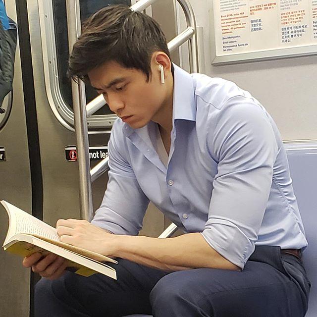 Hombre con rasgos asiáticos leyendo dentro del metro
