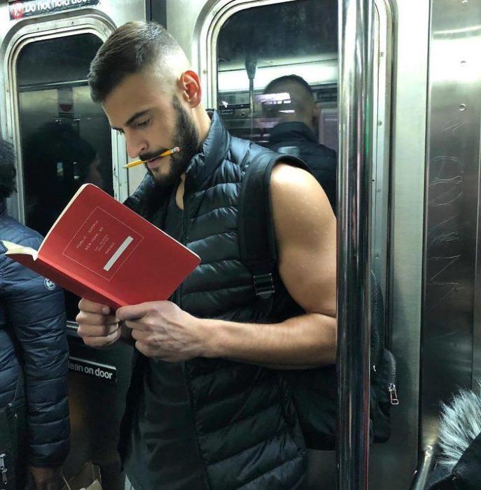Hombre llevando chaleco deportivo leyendo un libro rojo y sosteniendo un lápiz entre sus labios