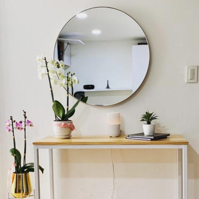 Artículos de decoración para el hogar; espejo grande y redondo con escritorio sencillo y macetas con flores