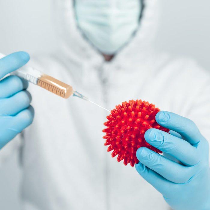 Médico sosteniendo una pelota roja con picos y una inyección con medicamento