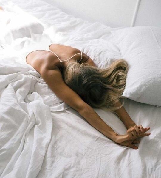 chica rubia estirándose en la cama