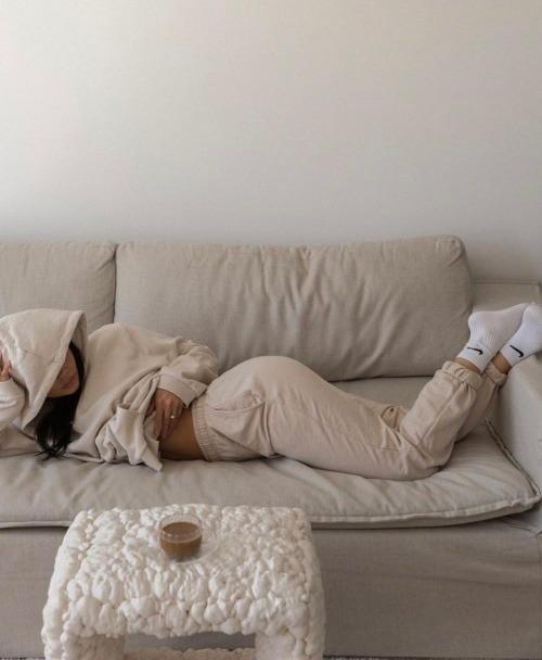 Chica con pants y sudadera beige acostada en un sillón