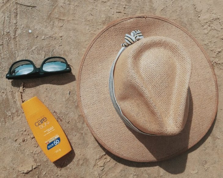 Beach hat, sunglasses and sunscreen on the sand