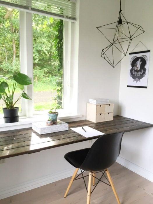 Escritorio con estilo minimalista,sobre una base de madera y silla color negro a juego con tonos blancos