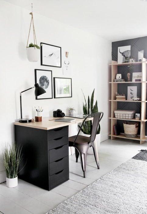Escritorio con estilo minimalista con escritorio negro y cajoneras, además de algunos cuadros como dorno