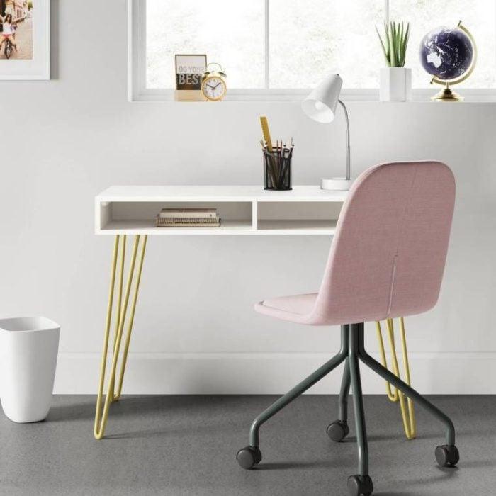 Escritorio con estilo minimalista con escritorio blnaco de patas delgadas y silla color rosa