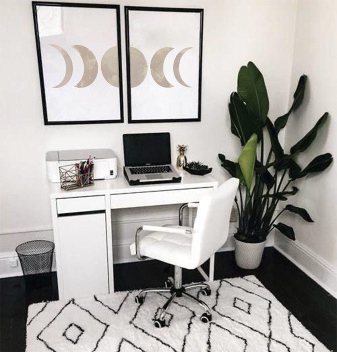 Escritorio con estilo minimalista en tonos blacos y una planta y cuadros como decoración