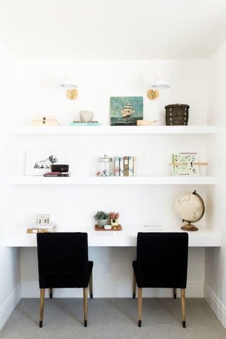 Escritorio con estilo minimalista para dos personas en tonalidades blancas y sillas negras
