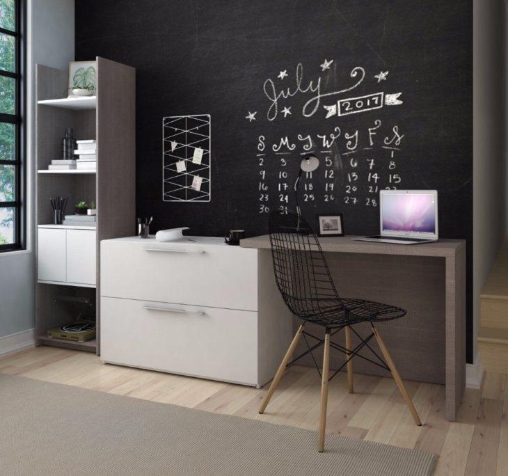 Escritorio con estilo minimalista, con cajones y repisas y pared negra para gis y silla de red