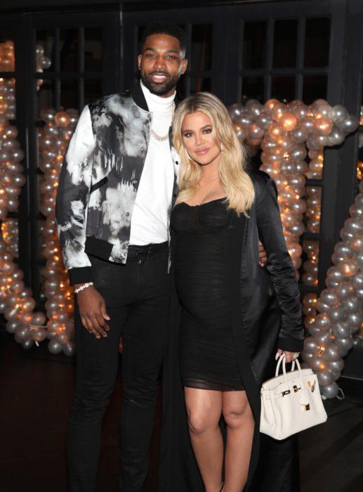 Khloé Kardashian y Tristan Thompson abrazados mientras están en una fiesta