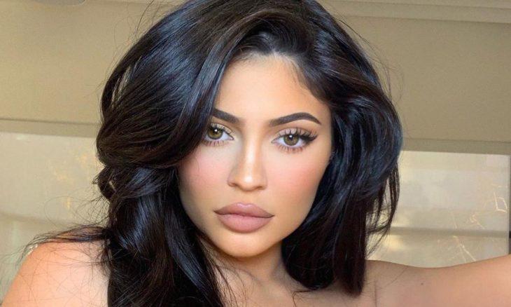 Kylie Jenner posando para una fotografía en la que muestra sus labios y el maquillaje hecho con sus productos