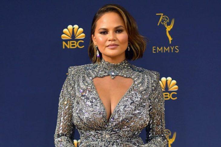 Chrissy Teigenusando un vestido de color plateado con brillos durante la alfombra roja de los EMYS de la cadena NBC