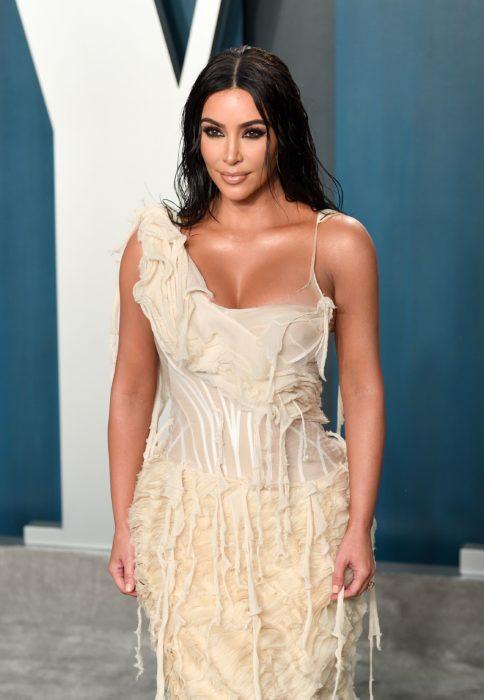 Kim Kardashian usando un vestido de color beige mientras posa para las cámaras del afther party de la revista Vanity Fair