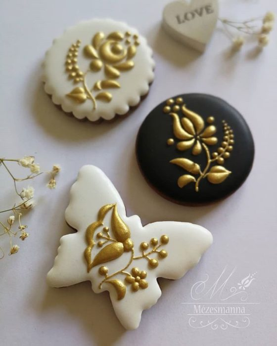 Galleta de jengibre decorada con flores en color dorado