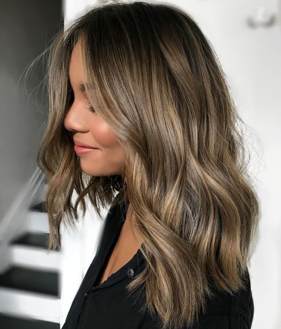Blonde girl with balayage in hair and gloss smudging effect