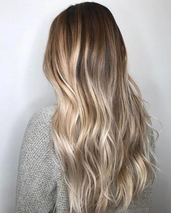 Chica rubia con balayage en el cabello y efecto Gloss smudging