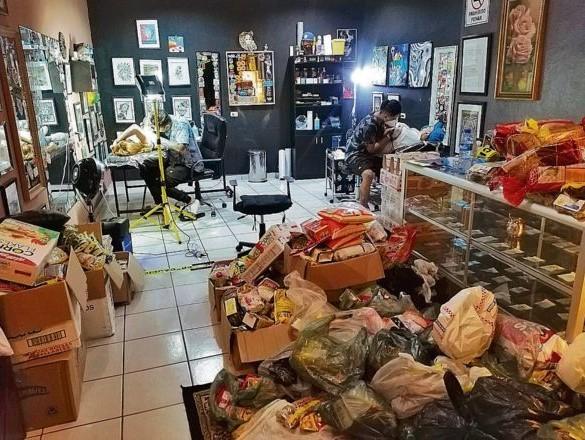 Hombres realizando tatuajes en un estudio repleto de víveres para donación