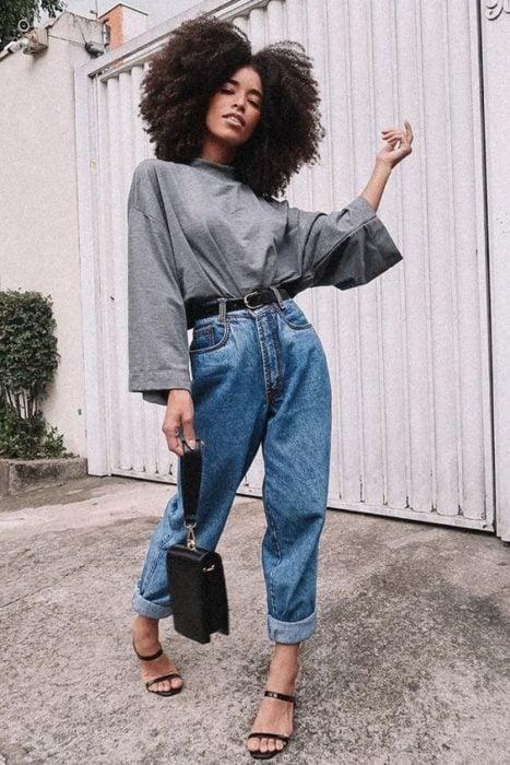 Chica morena con baggy pants de mezclilla y blusa gris
