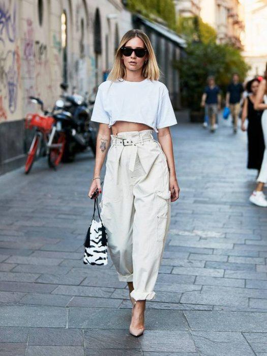 Mujer rubia con crop top blanco y baggy pants beige
