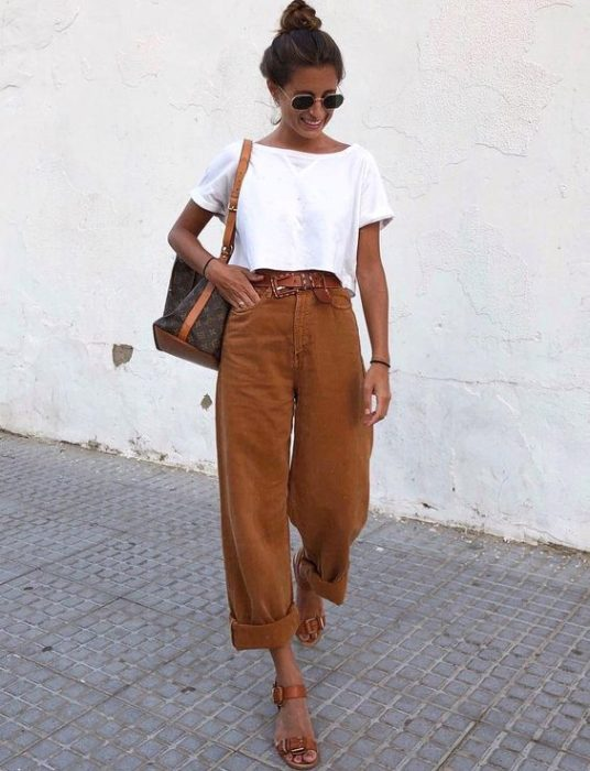 Woman posing in the street with white blouse and camel baggy pants