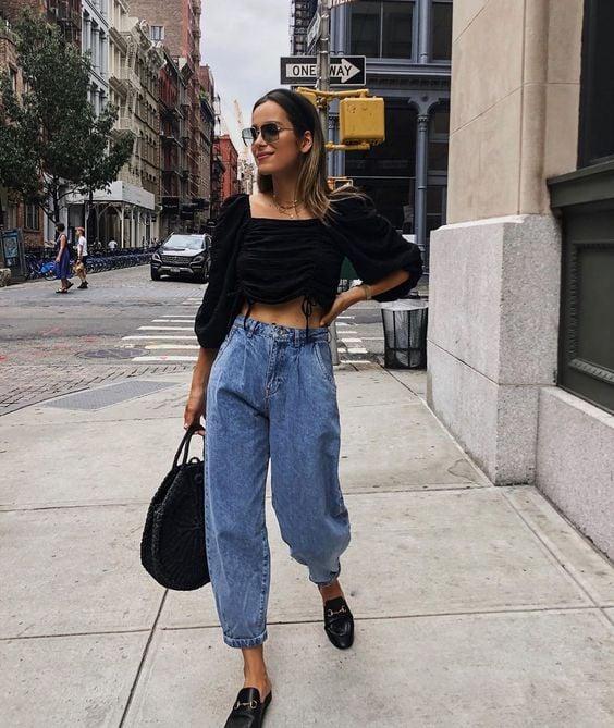 Chica caminado en la calle con baggy pants jeans y blusa negra tipo crop top
