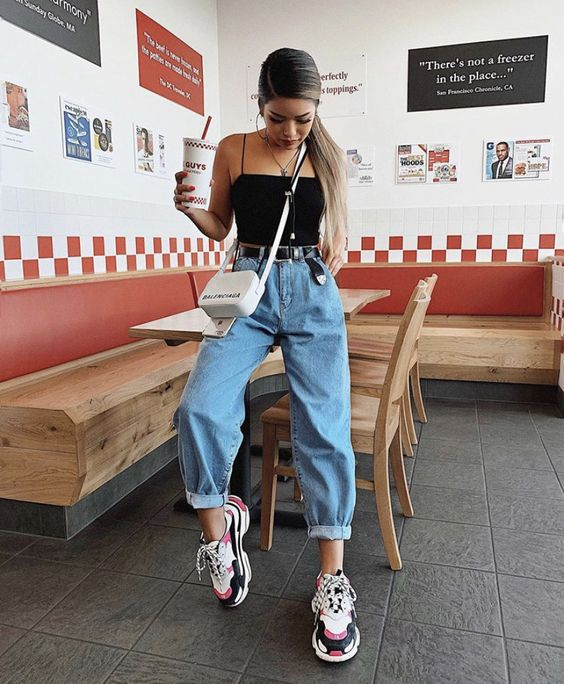 girl sitting at a table in denim baggy pants and black tank top