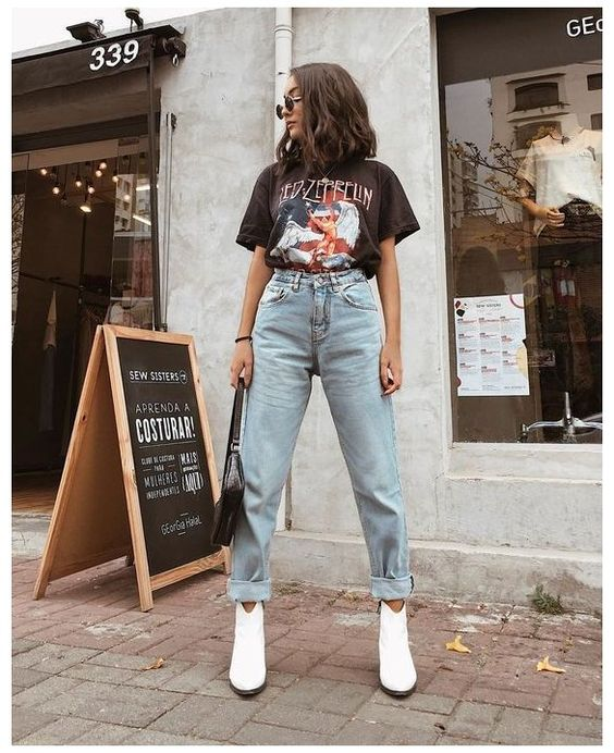 Girl standing on the street in baggy denim pants and black blouse