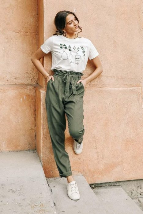 Girl leaning against the wall in green baggy pants and white blouse