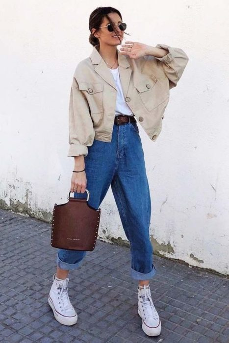 Girl walking in the street with baggy denim pants and beige jacket