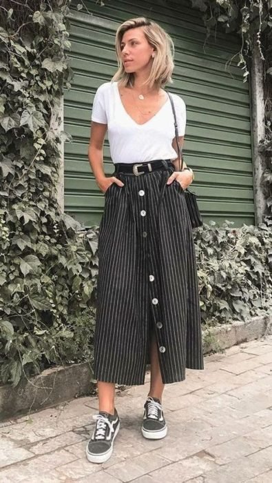 Blonde short hair girl in white blouse and black midi skirt
