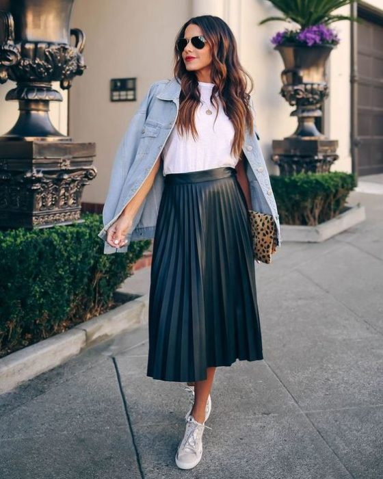 Brown Loose Hair Girl In White Blouse, Denim Jacket And Black Leather Midi Skirt With White Low Top Sneakers
