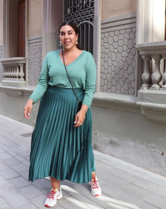 Curvy girl in green sweater and metallic green skirt with colorful sneakers